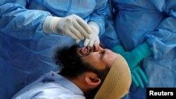 지난 8일 인도 아흐메다바다드에서 의사가 신종 코로나바이러스 진단 참가자의 검체를 채취하고 있다.