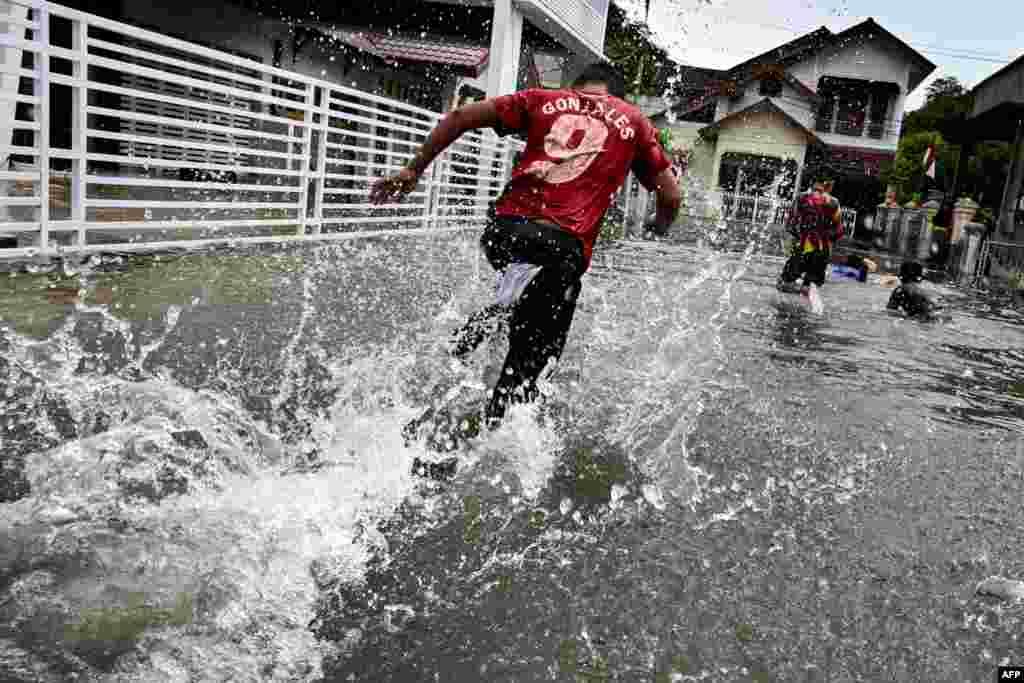 장마철 폭우로 거리가 물에 잠긴 인도네시아 반다아체에서 아이들이 뛰어가고 있다.