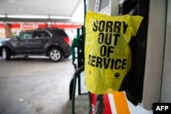 """FILE - An """"Out of Service"""" bag covers a gas pump as cars line up at a Circle K gas station near uptown Charlotte, North Carolina, May 11, 2021, after a ransomware attack shut the Colonial Pipeline, a major East Coast gasoline provider."""