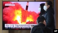 在韩国首尔火车站,人们经过一个电视屏幕显示新闻节目播出朝鲜发射导弹的画面(2020年3月29日)