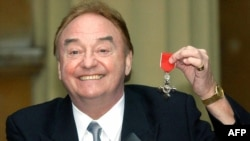 FILE - In this photo taken Dec. 12, 2003, sixties singing sensation Gerry Marsden poses with his MBE for services to Liverpudlian Charities at Buckingham Palace in London