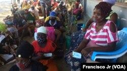 Deslocados, vítimas, da violência armada em Cabo Delgado aguardam na rua com as senhas para adquirir os seus produtos através da ajuda do em Pemba.