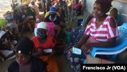 Deslocados, vítimas, da violência armada em Cabo Delgado aguardam na rua com as senhas para adquirir os seus produtos através da ajuda do PMA, em Pemba.