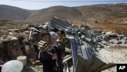 Seorang perempuan Palestina membawa anak-anaknya setelah rumahnya di Desa Aqraba, hancur. Aqraba terletak dekat permukiman Itamar, Nablus, West Bank.