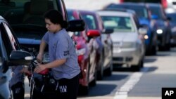 A customer pumps gas at Costco, as others wait in line, in Charlotte, N.C., May 11, 2021.
