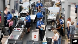 ماموران اداره امنیت ترابری ایالات متحده در حال رسیدگی به امور مسافران در فرودگاه بین المللی دنور. ۱۰ ژوئن ۲۰۲۰