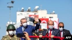 Presiden Turki Recep Tayyip Erdogan (kiri) dan pemimpin Siprus Turki Ersin Tatar (kanan), dalam parade di bagian utara ibu kota Siprus yang terbagi Nicosia, di Republik Turki Siprus Utara, 20 Juli 2021.