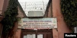 """FILE - A sign is seen above a house where police rescued men and boys in Kaduna, Nigeria, Sept. 27, 2019. The sign reads: """"Imam Ahmad Bun Hambal center for Islamic studies."""""""