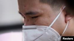 中国为死于冠状病毒病(COVID-19)的人举行全国哀悼活动,湖北省武汉市一名戴着口罩的男子哭泣。(2020年4月4日)