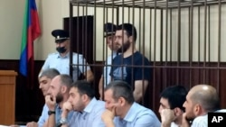 In this photo taken on June 16, 2019, Abdulmumin Gadzhiev, the religious affairs editor of the independent weekly Chernovik, stands in a cage in a court room in Makhachkala, the Caspian Sea province of Dagestan, Russia.