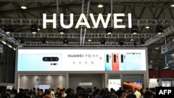 FILE - People gather at a Huawei stand during the Consumer Electronics Show, Ces Asia 2019 in Shanghai, June 11, 2019.