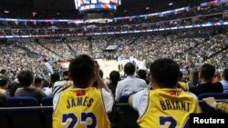 Fans in Lebron James and former player Kobe Bryant jerseys watch a game between the Los Angeles Lakers against the Brooklyn Nets, at Mercedes-Benz Arena, in Shanghai, China, Oct. 10, 2019. The NBA logos on their jerseys are covered up with Chinese flags.