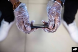 A passenger wears gloves to use his phone while waiting to board a flight at Toussaint Louverture International Airport, March 14, 2020, in Port-au-Prince, Haiti. As of Saturday, there were no reported cases of COVID-19 in Haiti.
