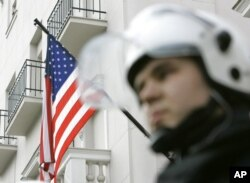 FILE - A Serbian officer protects the U.S. Embassy in Belgrade.