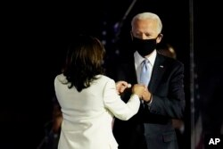 Presiden terpilih Joe Biden disambut di atas panggung oleh Wakil Presiden terpilih Kamala Harris sebelum dia berbicara di Wilmington, Delaware, Sabtu, 7 November 2020. (Foto: AP/Paul Sancy)