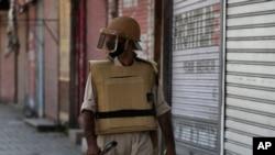 A Kashmiri policeman guards a closed shop in Srinagar, Indian-controlled Kashmir, Aug. 22, 2019.