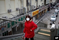 A woman wearing a protective face mask walks past closed restaurants amid a coronavirus outbreak, in Beijing, March 2, 2020.