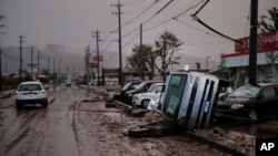 Typhoon-damaged cars sit on the street covered with mud, Oct. 14, 2019, in Hoyasu, Japan. Rescue crews dug through mudslides and searched near swollen rivers as they looked for those missing from typhoon Hagibis