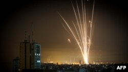 Rockets are seen in the night sky fired toward Israel from Beit Lahia in the northern Gaza Strip, May 14, 2021.