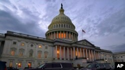 FILE - Dusk falls as Congressional leaders hash out a massive, year-end catchall bill, at the Capitol in Washington, Dec. 21, 2020.