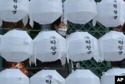 A woman wearing a face mask stands behind lanterns decorated for upcoming celebration of Buddha's birthday on April 30, at Jogye temple in Seoul, South Korea, Tuesday, Feb. 18, 2020.