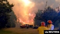 FILE PHOTO: Firefighters work at the scene of a bushfires in Bilpin, New South Wales, Australia in this still image from a social media video December 15, 2019. Andrew Mitchell/Cottage Point Rural Fire Brigade via REUTERS ATTENTION EDITORS - THIS…