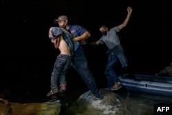 Migrantes de Centroamérica que cruzan ilegalmente de México a Estados Unidos para buscar asilo desembarcan de un bote inflable en el lado estadounidense del río Grande en la ciudad fronteriza de Roma el 29 de marzo de 2021.