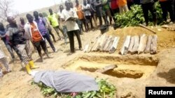 People attend the burial of Monday Doma, the student killed after gunmen stormed the Government Science Secondary School Kagara and kidnapped dozens, in Niger state, Nigeria, Feb. 17, 2021.