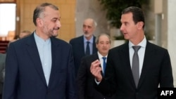 A handout picture released by the Syrian Arab News Agency shows Iranian Foreign Minister Hossein Amir Abdollahian, left, speaking with Syrian President Bashar al-Assad in the capital Damascus on Aug. 29, 2021.