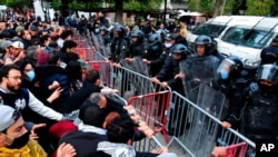 Demonstrators face police in Tunis, Jan. 23, 2021. Tunisia is extending its virus curfew and banning demonstrations as it tries to stem a rapid rise in infections and calm tensions after a week of protests over economic problems.