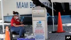 Članica biračkog odbora nosi zaštitnu opremu dok posmatra glasačku kutiju sa glasovima pristiglim poštom, tokom ranog glasanja, 7. avgusta 2020, u Miami Beachu, Florida.