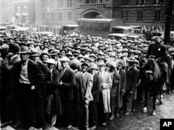 FILE - In this Oct. 9, 1930 file photo, thousands of unemployed people gather outside City Hall in Cleveland during the Great Depression.