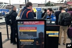 FILE - A health alert for people traveling to China is shown at a security checkpoint at Denver International Airport in Denver, Colo., March 2, 2020.