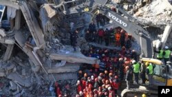 Rescue workers continue to look for people trapped under debris following a strong earthquake that destroyed several buildings on Friday, in Elazig, eastern Turkey, Sunday, Jan. 26, 2020. Working against the clock in freezing temperatures, Turkish…