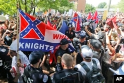 FILE- Members of the white supremacist KKK are escorted by police past a large group of protesters during a KKK rally in Charlottesville, Va., July 8, 2017.