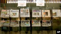 Newspapers headlining Prince Harry and Meghan's explosive TV interview are displayed for sale outside a shop in London, March 9, 2021.