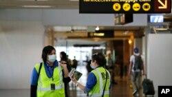 Dua pekerja di bandara internasional Seattle-Tacoma, negara bagian Washington, AS mengenakan masker di tengah perebekan virus corona di sana.