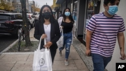 Emili Prado, 21, left, legal liaison for La Colmena, a community-based organization working with immigrant workers, walk with volunteers Christine Cuenca, 18, center, and Jason Jimenez, 19, right, to deliver information local business in a campaign…