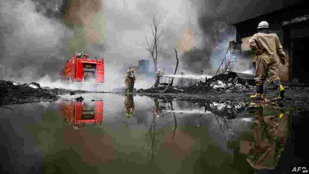 인도 델리의 창고에 화재가 발생한 후 출동한 소방대원들이 진화작업을 벌이고 있다.