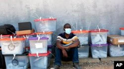 A polling agent sits next to ballot boxes as vote counting continues at various stations in Lusaka, Zambia, Aug. 13, 2021.