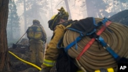 Two firefighters from Cosumnes Fire Department carry water hoses while holding a fire line to keep the Caldor Fire from spreading in South Lake Tahoe, Calif., Sept. 3, 2021.