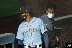 "Seattle Mariners' Mallex Smith, left, and Dee Gordon, right, wear masks as they enter the dugout, Monday, July 20, 2020, during a ""summer camp"" baseball scrimmage game in Seattle. (AP Photo/Ted S. Warren)"