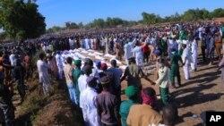 Des gens assistent à des funérailles pour les personnes tuées par des militants présumés de Boko Haram à Zaabarmar, au Nigéria, le dimanche 29 novembre 2020.