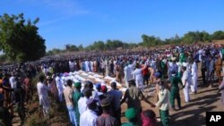 People attend a funeral for those killed by suspected Boko Haram militants in Zaabarmar, Nigeria, Sunday, Nov. 29, 2020. Nigerian officials say suspected members of the Islamic militant group Boko Haram have killed at least 40 rice farmers and…