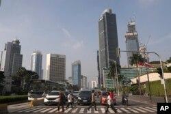 Orang-orang yang memakai masker wajah menyeberang jalan di kawasan bisnis utama di Jakarta yang terlihat sepi, Senin, 8 Juni 2020. (Foto: AP)
