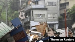 A resident looks from a window at houses that have been damaged by a mudslide following heavy rain at Izusan district in Atami, Japan, July 3, 2021. (Kyodo/via Reuters)