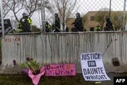 Flores y letreros dejados frente a una valla de seguridad al comienzo del toque de queda para protestar por la muerte de Daunte Wright, fallecido a manos de una oficial de policía en Brooklyn Center, Minnesota, el 12 de abril de 2021.