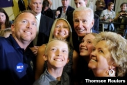 Democratic 2020 U.S. presidential candidate and former Vice President Joe Biden takes photos with supporters at an event at Iowa Wesleyan University in Mount Pleasant, Iowa, June 11, 2019.