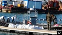 Arhiv - Pripadnici Obalne straže Tunisa stoje pored tijela utopljenih migranata, u luci u Sfaksu, 24. decembra 2020.