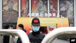 A security officer wearing a mask and a cap with the Chinese national flag guards the entrance after a World Health Organization team's arrival at an exhibition on the fight against the coronavirus, in Wuhan, China, Jan. 30, 2021.